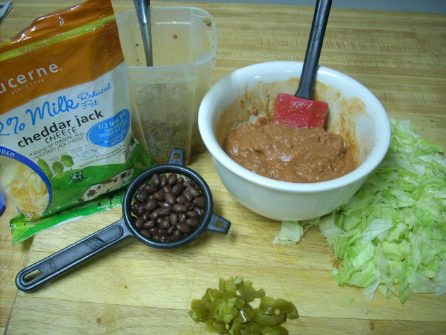 enchilada/refried bean mix, black beans, taco meat, mexican cheese, jalapenos for me and shredded lettuce!